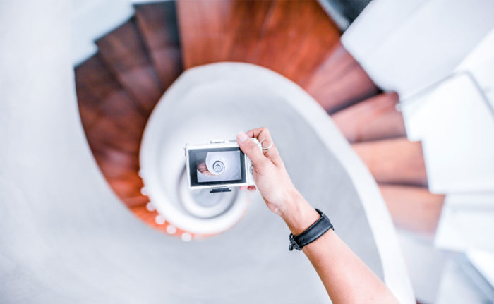 Hand holding a camera, taking a photo of a stairwell